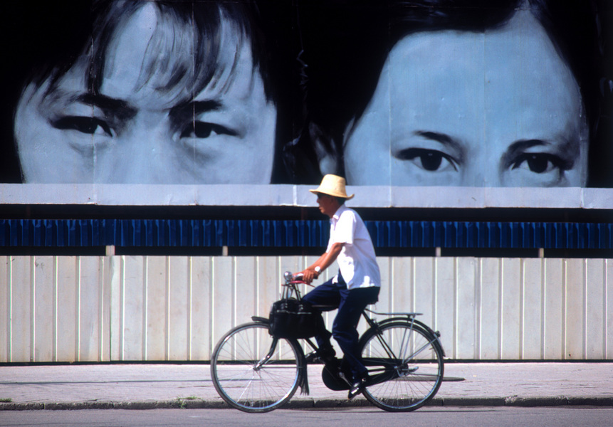 Eyes on a billboard watch a bicyclist on a Beijing street. © 1986 by Mark Avery