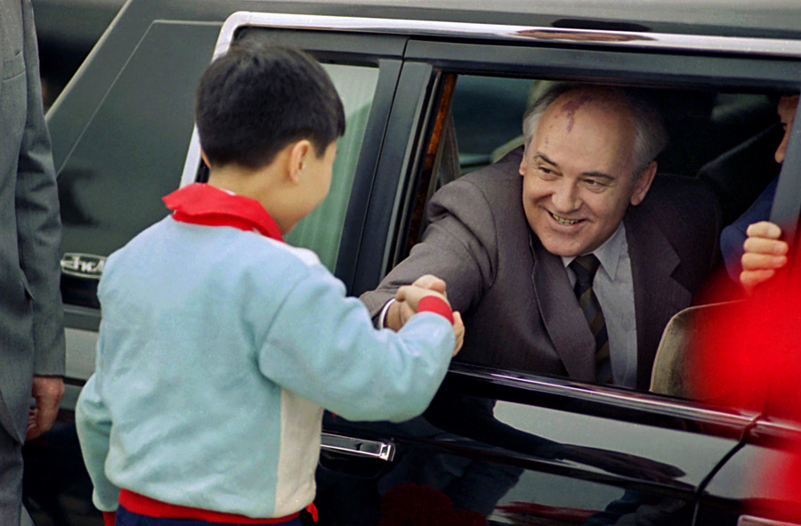 Soviet General Secretary Mikhail Gorbachev leans out of the window of his limousine to shake the hand of a Chinese child on hand to greet him as he arrived at Shanghai Airport. © 1989 AP Photo/Mark Avery