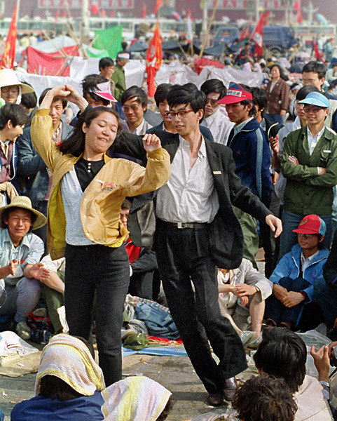 A young couple, two out of thousands of university students who occupying Tiananmen Square for nine days, pass the time with a lively dance. © 1989 AP Photo/Mark Avery