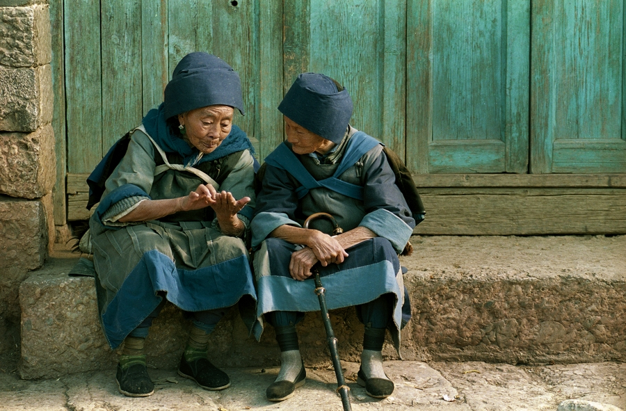 Two elderly Naxi women gossip near the central market in Lijiang, China. © 1990 AP Photo/Mark Avery
