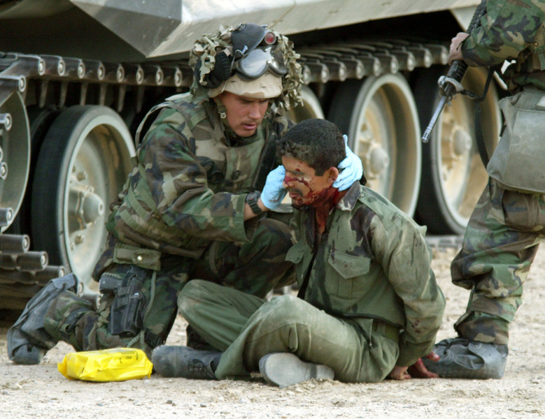 Navy Corpsmen tend to a wounded Iraqi prisoner after Marines took control of an oil pumping station in southern Iraq on the first morning of the invasion. © 2003 Mark Avery/Orange County Register