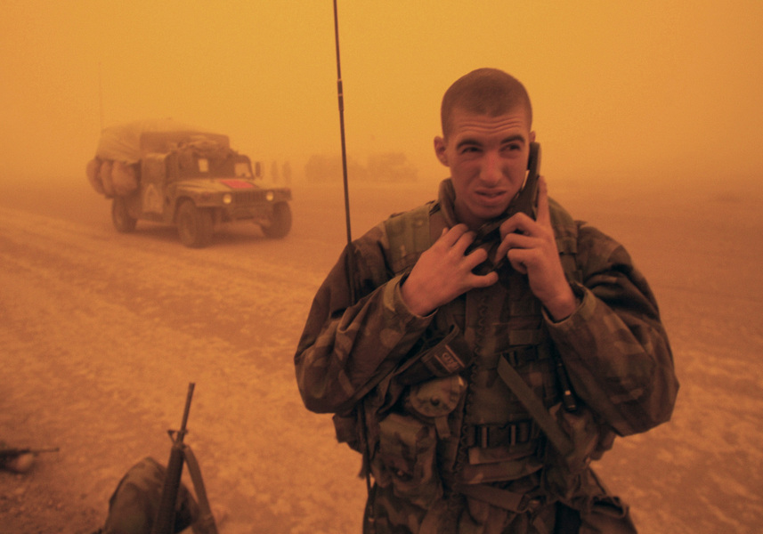 Radio operator L/Cpl Brad Rusher of Carthage, SD, maintains radio contact with an artillery battery in a sandstorm during the invasion of Iraq. © 2003 Mark Avery/Orange County Register