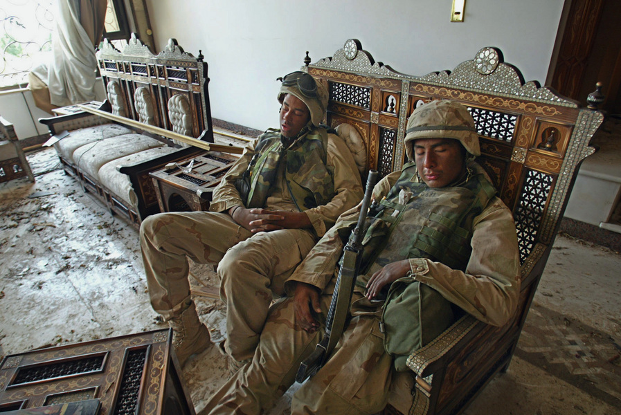 L/Cpl. Dominic Chevalier, left, of Pittsburg, CA, and L/Cpl. Leonardo Morales of Los Angeles sleep in fancy chairs in one of Saddam Hussein's palaces, taken by 1st battalion/5th Marines in Baghdad. © 2003 Mark Avery/Orange County Register