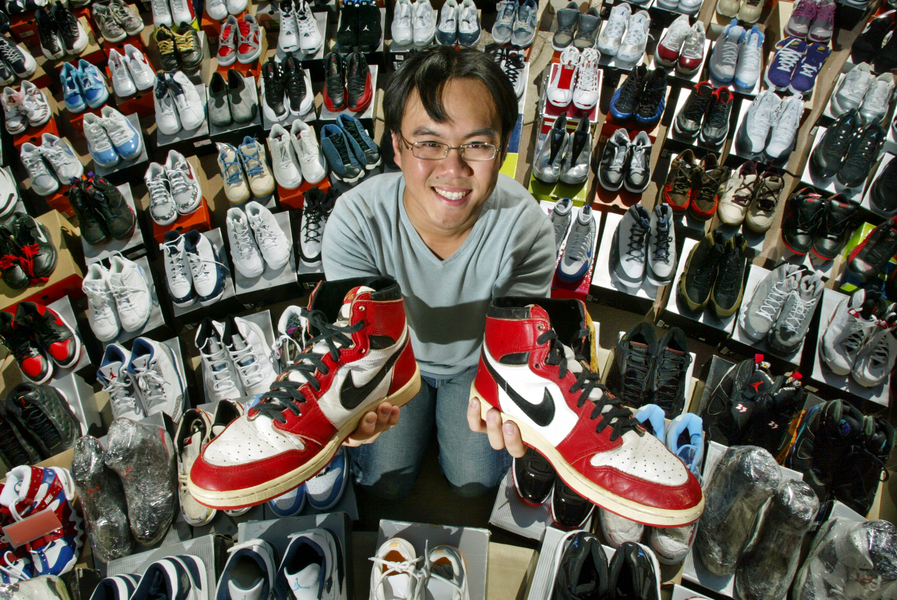 Collector Eric Hsieh of Irvine with most of his 175 pairs of sneakers. He holds a pair of original Nike Air Jordans from 1984. © 2004 Mark Avery/Orange County Register