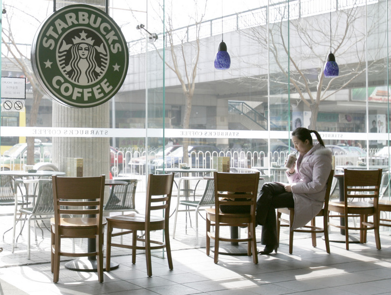 A young Chinese woman enjoys a quiet moment at a Beijing Starbucks. © 2006 by Mark Avery
