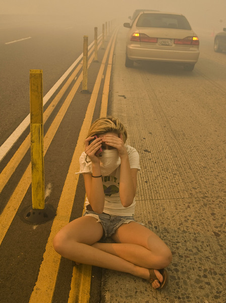 Amanda Derse tries to shield herself from the smoke as she sits in the freeway after a brush fire shut down west bound Interstate 91 in Yorba Linda © 2008 AP Photo/Mark Avery